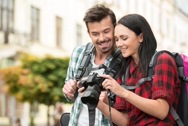 Un couple heureux regarde des images sur l'appareil photo.