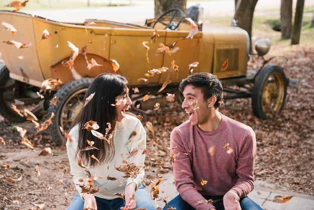 Couple heureux remuant les feuilles d'automne et se regardant