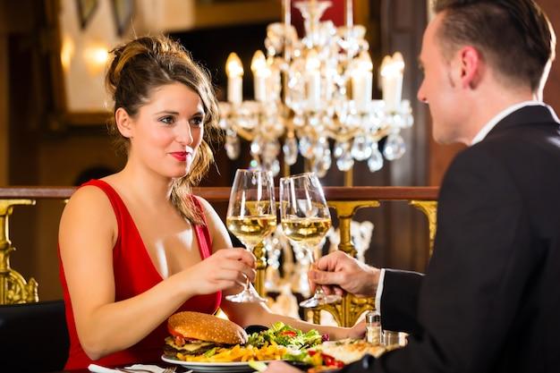 Couple heureux a un rendez-vous romantique, un restaurant raffiné, un grand lustre