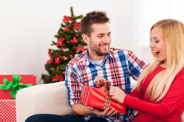 Couple heureux s'amuser lors du cadeau de noël d'ouverture