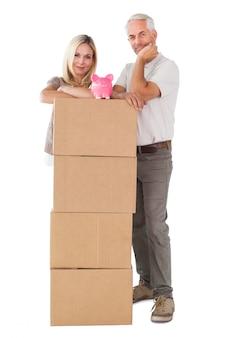 Couple heureux, s'appuyer, pile, de, déménagement, boîtes, à, tirelire