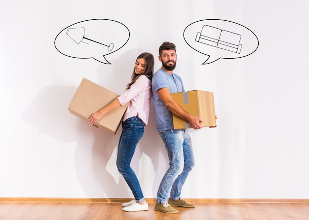 Couple heureux s'installant dans une nouvelle maison, ouvrant des boîtes.