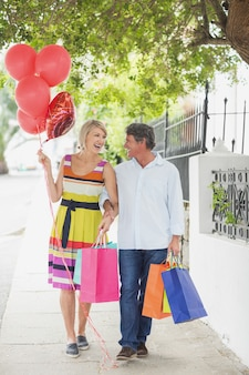 Couple heureux avec des sacs et des ballons