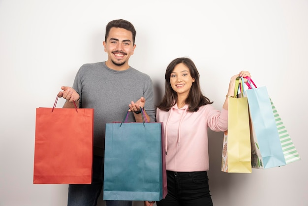 Couple heureux avec des sacs à provisions debout sur blanc.