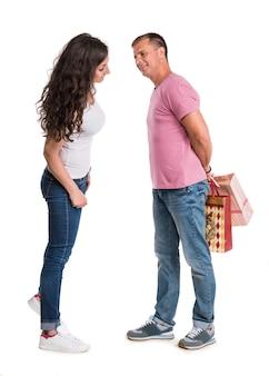 Couple heureux avec des sacs à provisions sur un mur blanc