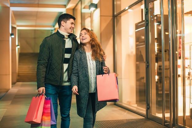 Couple heureux avec des sacs à provisions, profitant de la nuit en ville