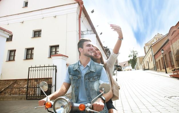 Couple heureux sur scooter faisant selfie photo sur smartphone à l'extérieur