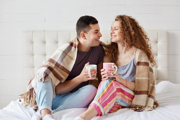Couple heureux se détendre au lit avec une boisson chaude, tient des tasses pleines de thé ou de café, s'asseoir sous une couverture chaude, s'habille avec désinvolture, jeune famille romantique