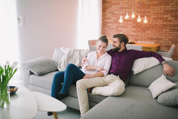 Couple heureux se détendre sur le canapé