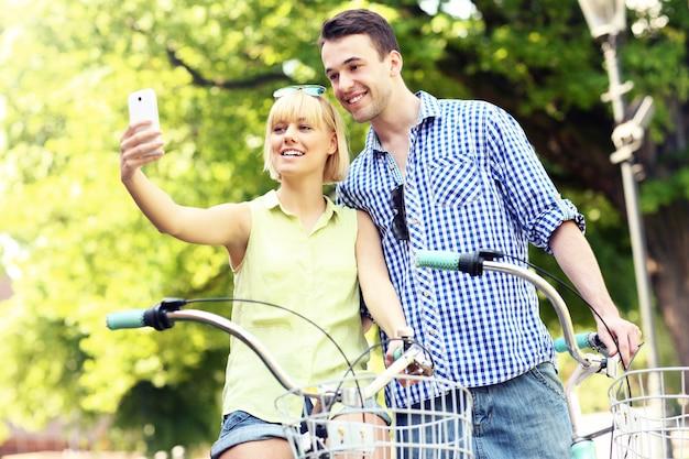 Un couple heureux se prenant en photo à vélo