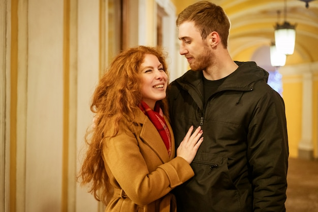 Un couple heureux se tient dans une étreinte dans la rue le soir dans les lumières festives
