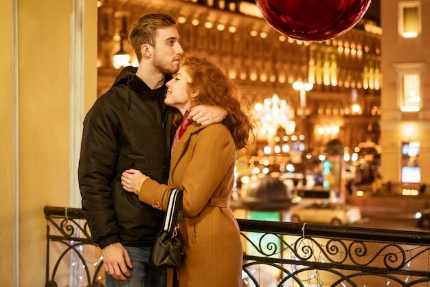 Un couple heureux se tient dans une étreinte dans la rue le soir dans les lumières de fête