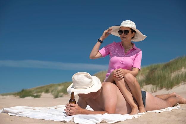 Un couple heureux et séduisant se détend sur la plage - un homme boit de la bière et une femme est assise sur le dos.