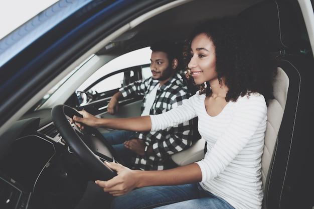 Couple heureux souriant assis dans une voiture