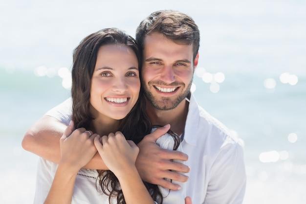 Couple heureux souriant à la caméra