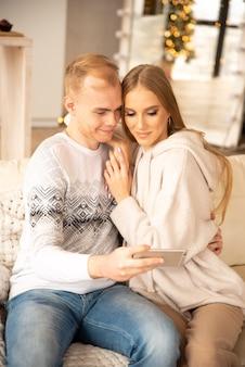 Couple heureux avec téléphone portable en ligne pour féliciter noël. ils sourient et célèbrent les vacances d'hiver.