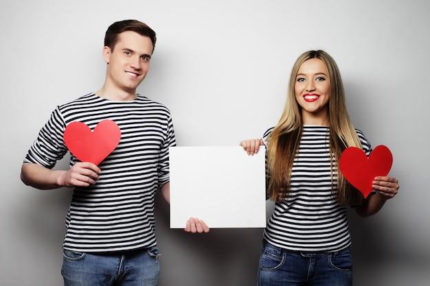 Couple heureux tenant des coeurs blancs blancs et rouges.
