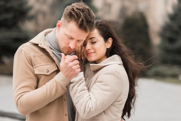 Couple heureux, tenant mains, dehors
