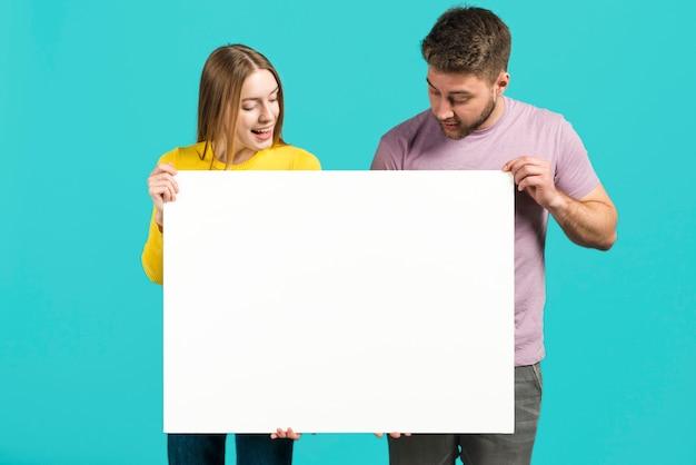 Couple heureux tenant une pancarte blanche