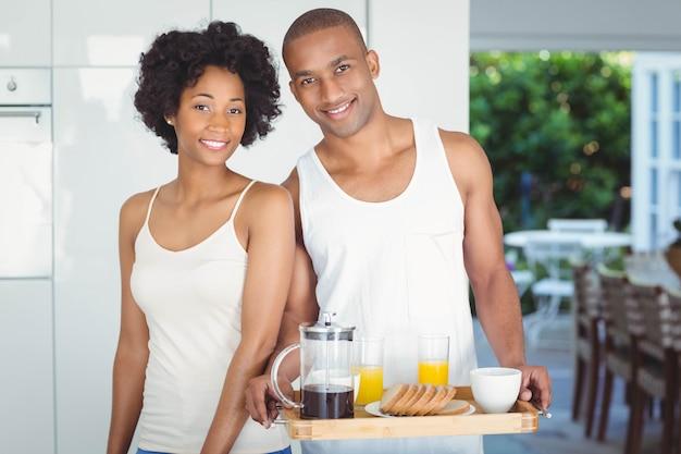 Couple heureux tenant un plateau de petit déjeuner dans la cuisine à la maison