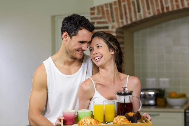 Couple heureux tenant un plateau de petit déjeuner dans la cuisine