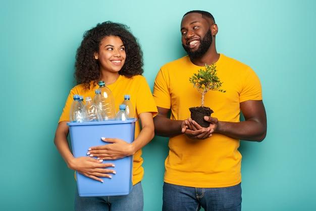 Couple heureux tenir un récipient en plastique avec des bouteilles et un petit arbre sur une couleur bleu clair. concept d'écologie, de conservation, de recyclage et de durabilité