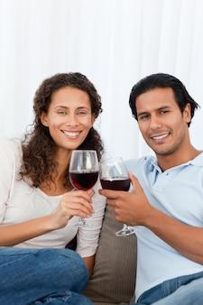 Couple heureux tinter les verres de vin rouge sur le canapé