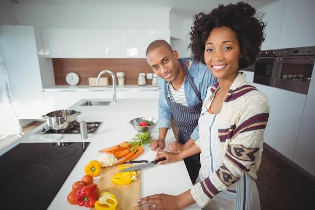 Couple heureux en train de préparer des légumes dans la cuisine