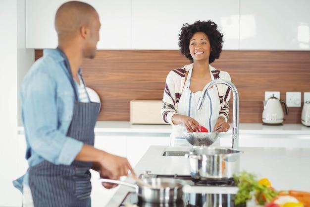 Couple heureux en train de préparer un repas dans la cuisine