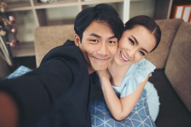Couple heureux en train de rire et de prendre un selfie avec téléphone assis sur un canapé à la maison