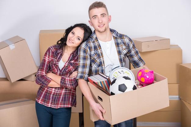 Un couple heureux transporte des cartons de déménagement en carton.