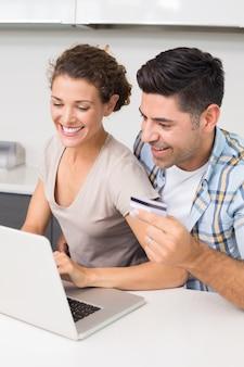 Couple heureux utilisant un ordinateur portable ensemble pour magasiner en ligne