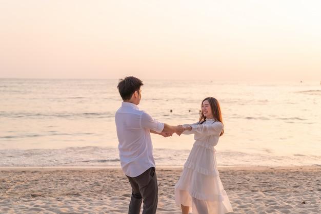 Couple heureux va lune de miel voyage sur la plage de sable tropicale en été