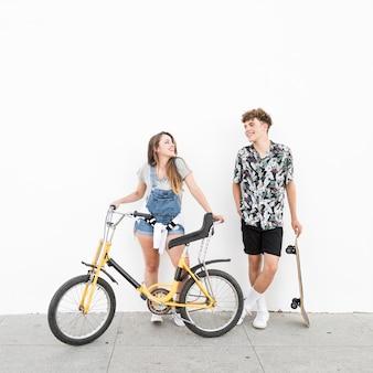 Couple heureux avec vélo et planche à roulettes se regardent