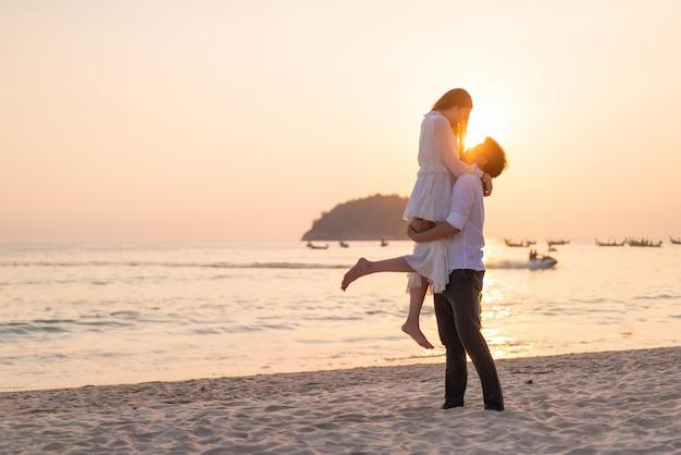 Couple heureux en voyage de noces sur la plage de sable tropicale en été