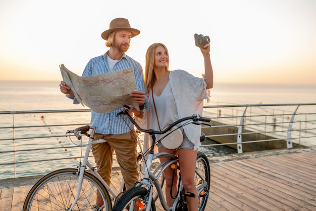 Couple heureux voyageant en été sur des vélos, à la recherche de visites de la carte et à prendre des photos