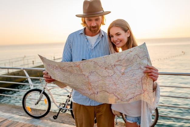 Couple heureux voyageant en été sur des vélos, à la recherche de visites de la carte