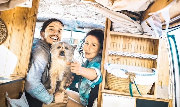 Couple de hipster avec un chien mignon voyageant ensemble sur un mini-van de transport oldtimer