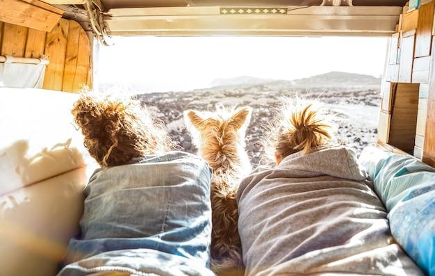 Couple de hipster avec un chien mignon voyageant ensemble sur un transport en van vintage