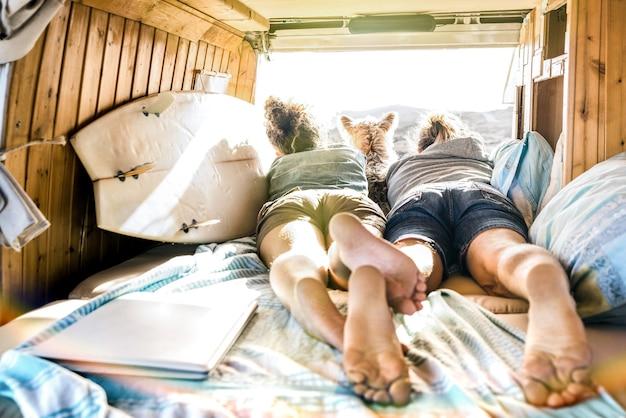 Couple hipster avec chien voyageant ensemble sur le transport van vintage
