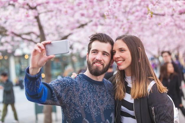 Couple de hipster prenant un selfie à stockholm avec des fleurs de cerisier