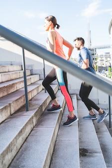 Couple hispanique courant ou faisant du jogging ensemble à l'extérieur.