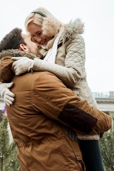 Couple en hiver étreignant vue basse