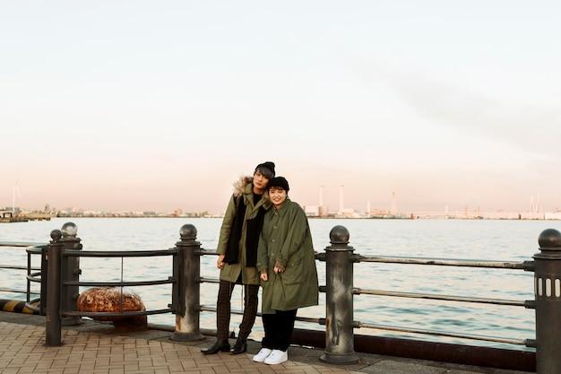 Couple d'hiver plein coup posant à l'extérieur