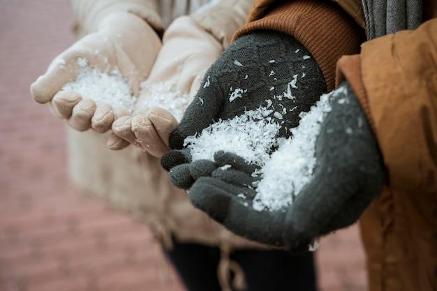 Couple en hiver tenant la neige dans leurs mains