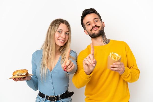 Couple holding hamburger et frites sur fond blanc isolé montrant et levant un doigt