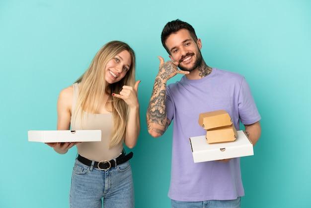 Couple holding pizzas et hamburgers sur fond bleu isolé faisant un geste téléphonique. rappelle-moi signe