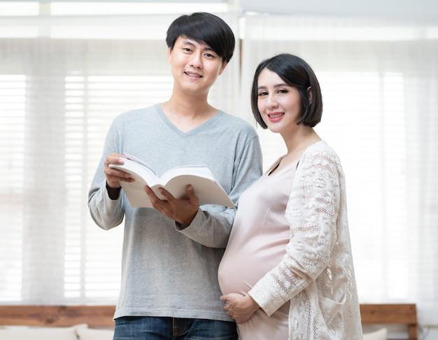 Couple, homme asiatique, et, femme enceinte, livre lecture, dans maison