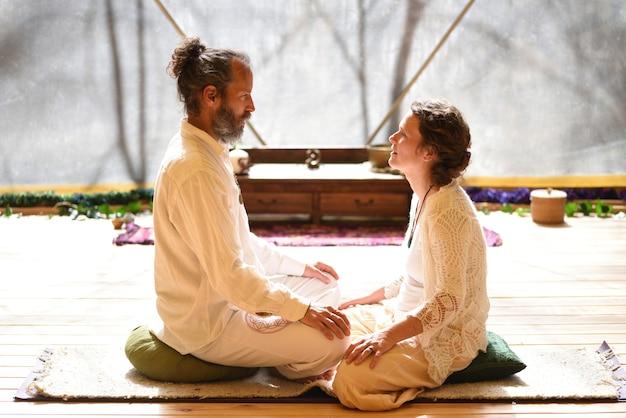 Couple homme et femme assis en posture de lotus dans la pratique du yoga tantrique.
