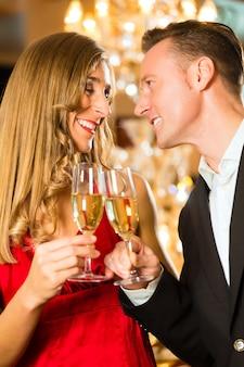 Couple, homme et femme, buvant du champagne dans un restaurant gastronomique, chacun tenant un verre de vin mousseux à la main
